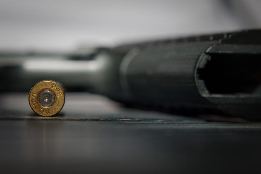 A bullet (in color) resting next to a gun (in black-and-white.)