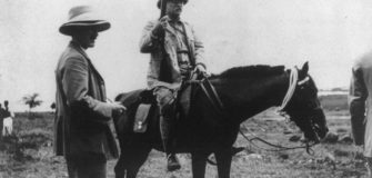 Theodore Roosevelt sitting astride a horse and holding a musket.
