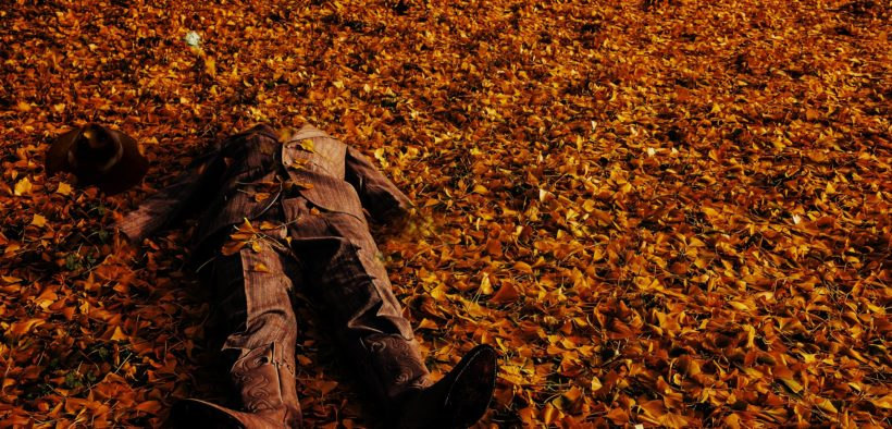 A mockup of a man's body in a suit on the ground with leaves scattered everywhere.