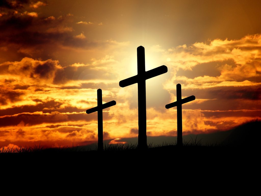 Three crosses silhouetted at sunset.
