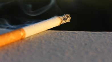 A lit cigarette burning on a ledge.