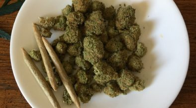 Marijuana buds and rolled joints sitting on a white plate.