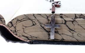 A cross on a chain sitting on an open Bible.