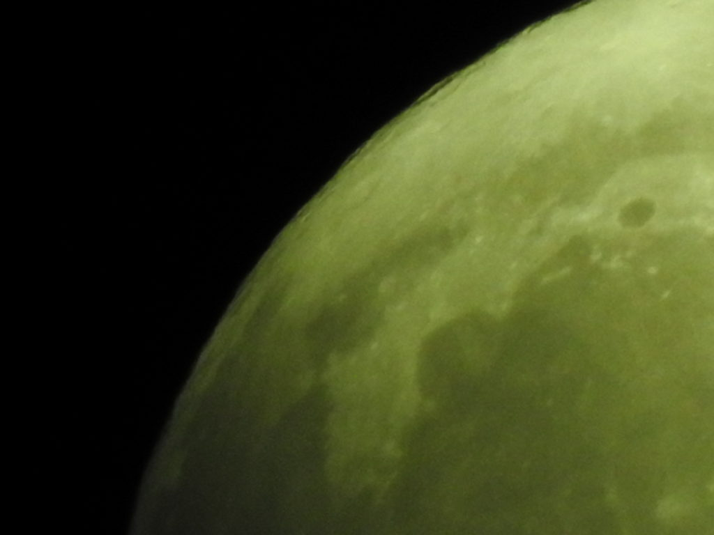 Close-up of moon with green hue.