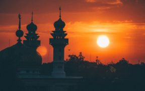 A mosque silhouetted against the sky at sunrise.