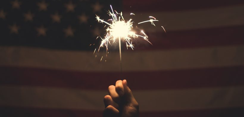 A hand holding a sparkler in front of an American flag.