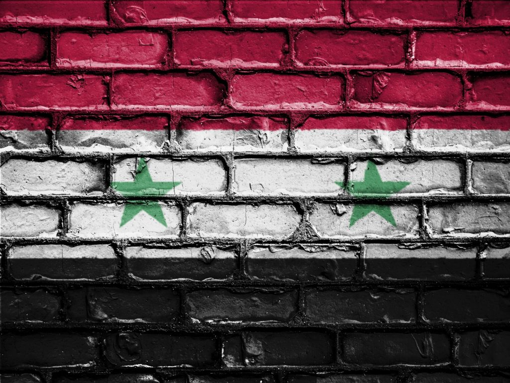 A Syrian flag painted on a brick wall.