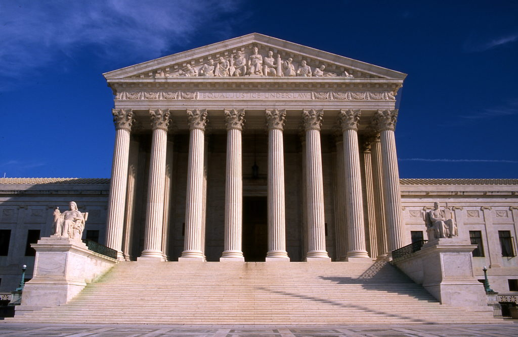 Supreme Court building from outside underneath a blue sky.