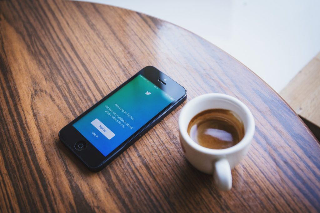 Mobile phone on a table next to a mug full of coffee.