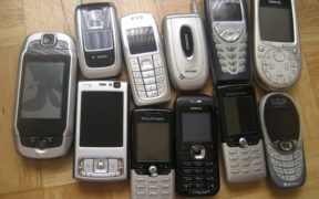 Old-model cellular phones lined up on a table.