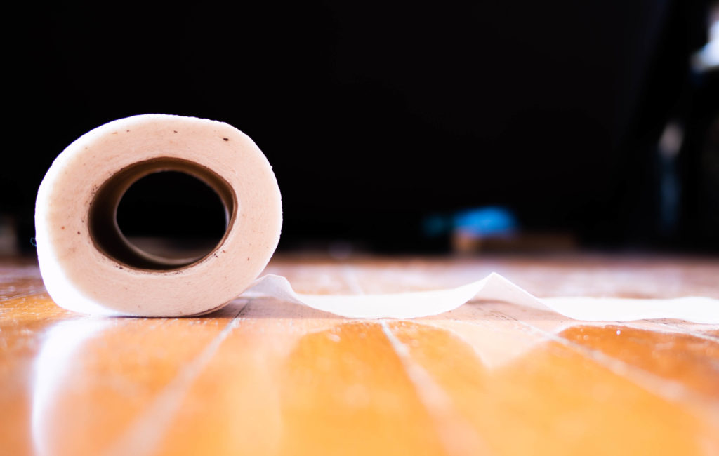 Roll of toilet paper on a hardwood floor.