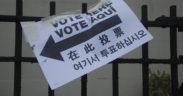"Sign reading ""Vote Here"" in several different languages."