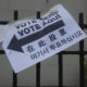 """Sign reading """"Vote Here"""" in several different languages."""