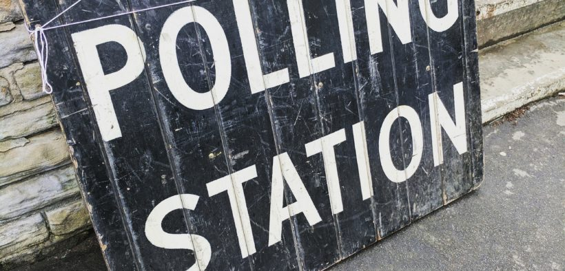 "Old, weathered sign saying ""POLLING STATION."""