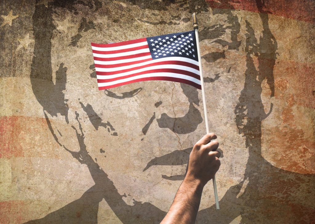 Donald Trump's face painted on a wall with a man's arm waving an American flag in front of it.