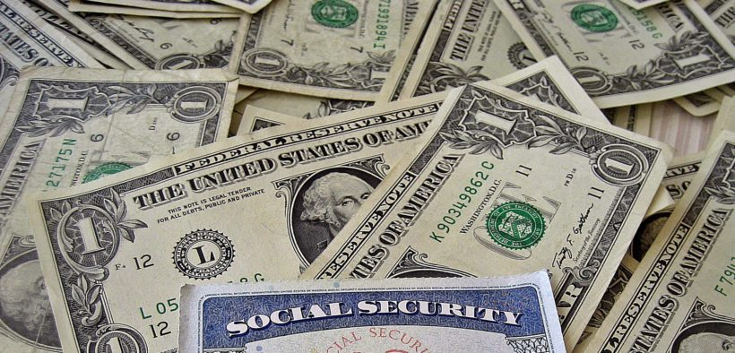 Social Security card atop a pile of United States dollars.