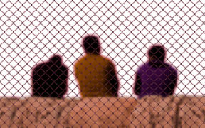 Three men sitting behind a chain link border fence.
