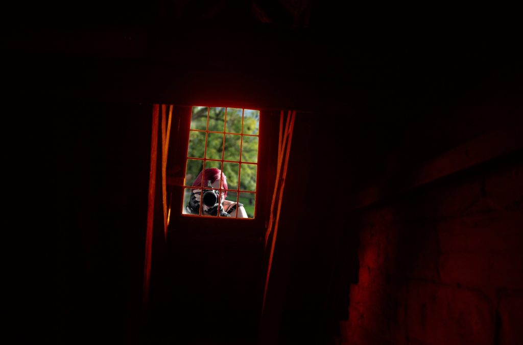Woman at a window taking photos of the inside of a home.
