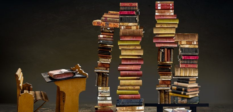 Writing desk and stacks of books.