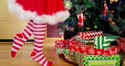 A person's legs in red and white striped socks and a white-trimmed red skirt next to a Christmas tree.
