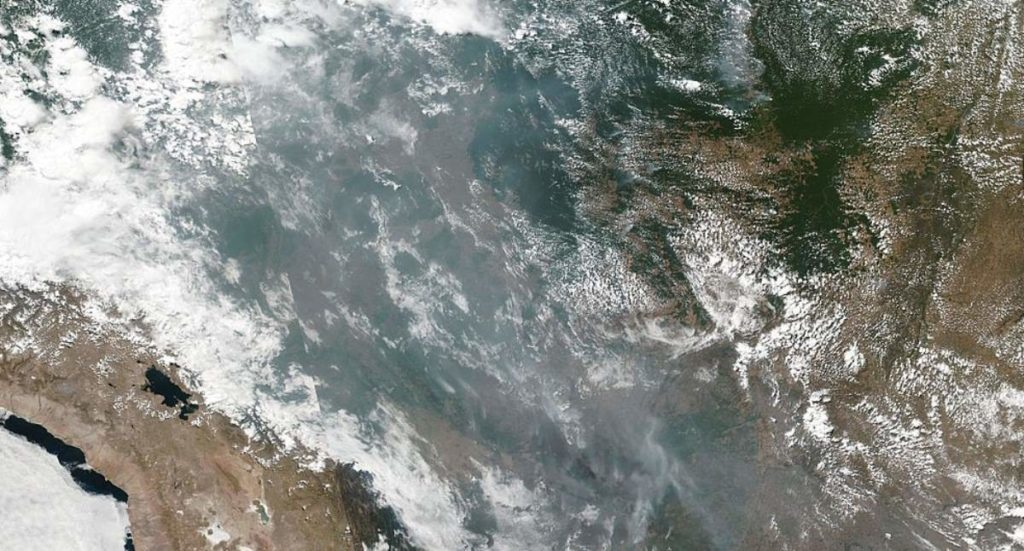 Photograph showing smoke and fires burning the Amazon Basin from space.