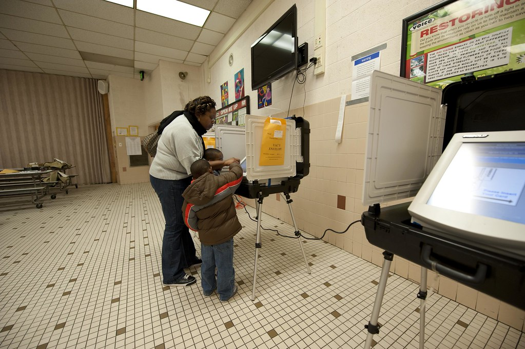 A woman with two children at an electronic voting machine.