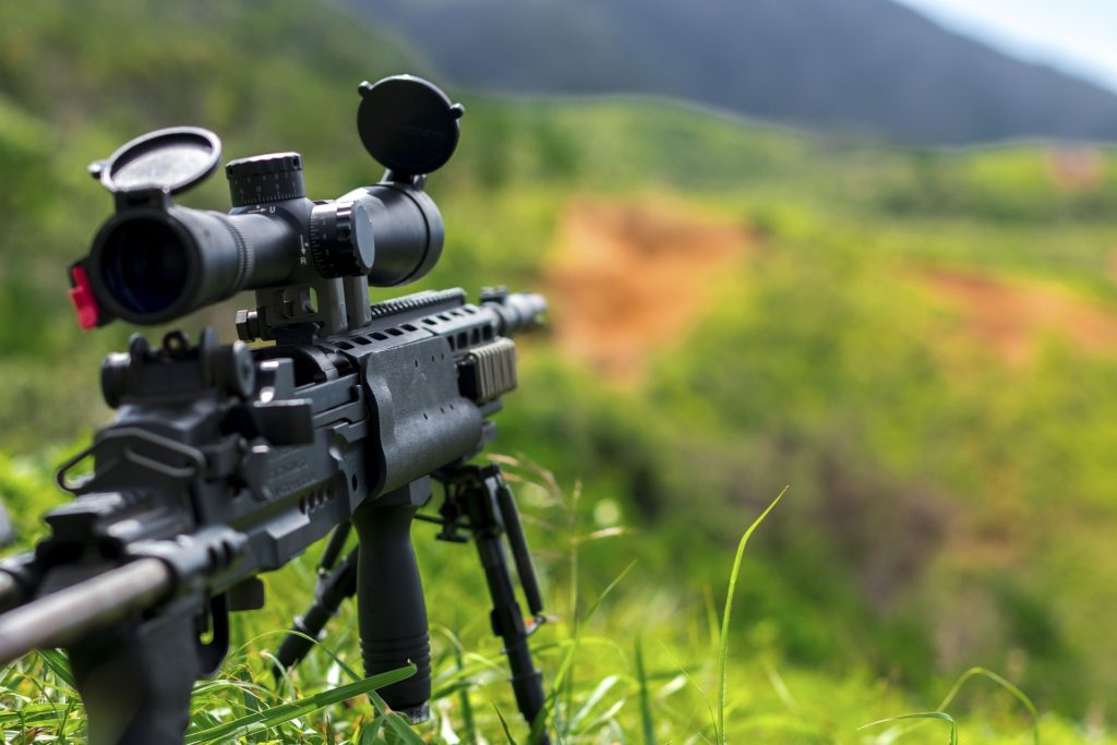 An unmanned rifle overlooking a grassy knoll.