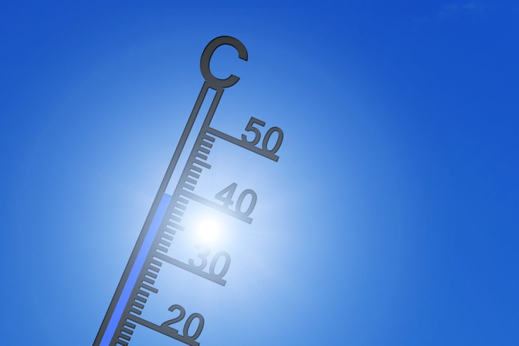 A thermometer showing 35 degrees Centigrade, or around 100 degrees Fahrenheit, against a clear blue sky.