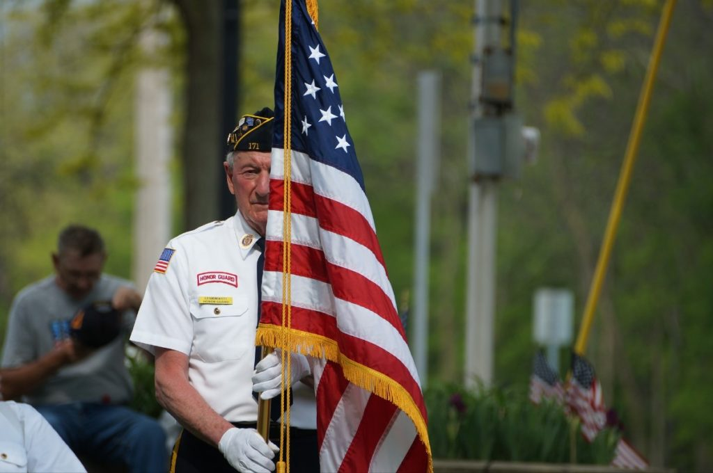 A veteran carrying an American flag.