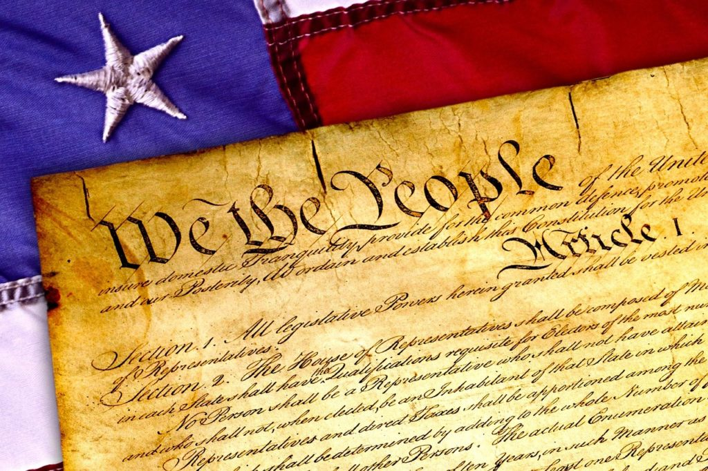 A stylized image of the United States Constitution on top of an American flag.