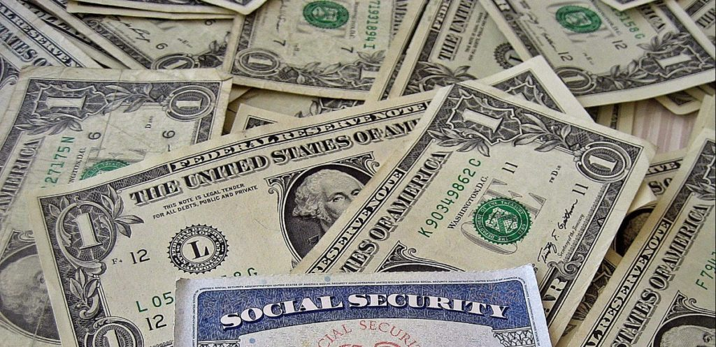 A social security card sitting on top of a bed of American dollar bills.